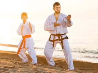 Man and boy exercising karate