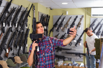 Young man is taking selfie on phone with air gun