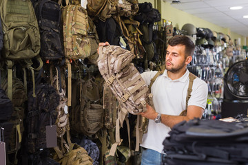 Man choosing textile backpack gun in military shop