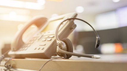 close up soft focus on headset with telephone devices at office desk for customer service support concept