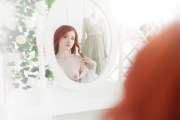 Tender portrait of a young dreamy redhead woman wearing beautiful vintage dress. She is sitting in front of the mirror with naked breast.