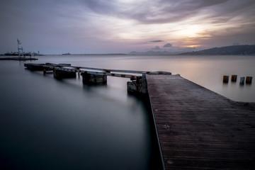 Un vieux ponton en ruine qui avance sur la mer lors d'un magnifique couché de soleil