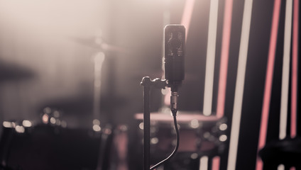 Microphone in recording Studio or concert hall close-up, with drum set on background out of focus.