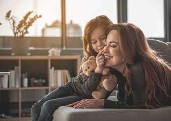 Portrait of smiling woman and child lying on sofa. Little girl is touching her mom nose with her finger holding teddy bear. Cute family is happy and looking perfect
