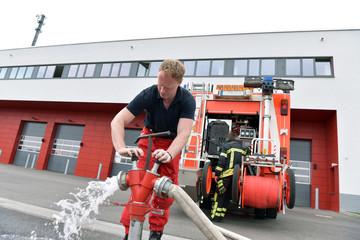 Feuwehrmann am Löschfahrzeug befüllt Fahrzeug mit Wasser zur Bekämpfung von Bränden // Fireman at fire engine fills vehicle with water to fight fires
