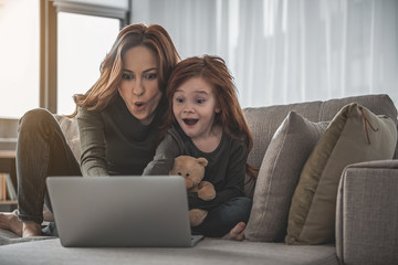 Look. Full length portrait of mother and kid sitting on sofa and looking on laptop with astonishment. They are pointing their fingers into the screen with their mouth open in excitement