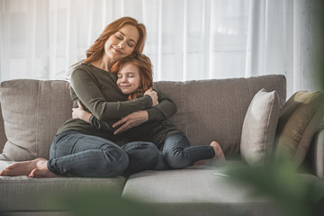My dearest. Full length portrait of mother and her child hugging each other and sitting on couch at home. They are smiling, calm and happy