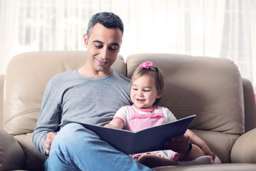 Happy Little Girl And Father Reading Book Together At Home