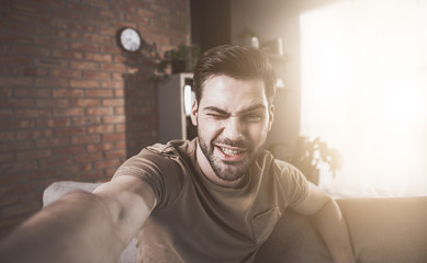 Playful mood. Portrait of stylish bristled guy is taking selfie. He is smiling while sitting on cozy couch at home and winking at camera. Sunlight in background