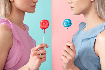 Side view profile of female lower face holding colorful candies on stick. They are calm. Isolated on blue and pink background