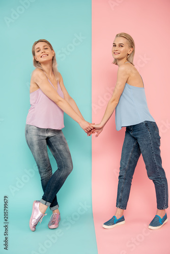 0092c3c44 Full length portrait of two cheery female friends holding hands and ...