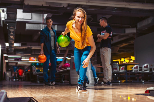 Young woman throwing bowling ball