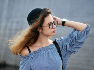 Young beautiful student girl in blue blouse and trendy glasses having fun posing on a river pier in city park