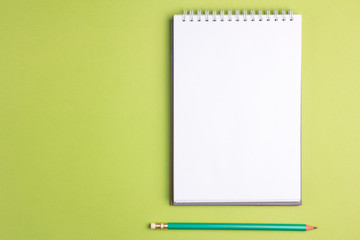 Blank notebook with pencil on green pastel background. Flat lay concept. Copy space