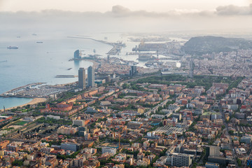 Aerial view of Barcelona city with port and harbor at sunset, Spain.