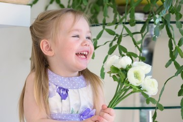 Beautiful little smiling blond girl in dress holds bouquet of Ranunculus