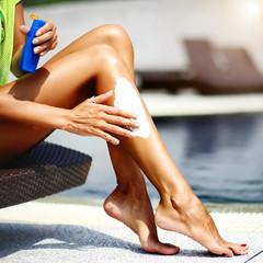Woman applying sun protection lotion on legs