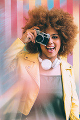 Mixed race woman in a colorful artwork background wall holding a vintage camera