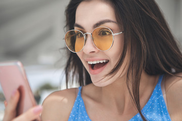 Portrait of cheerful young woman is reading message om her smartphone. She is looking at screen with excitement and laughing