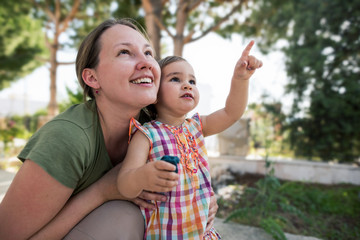 Mother And Little Child Girl Outdoors Looking At Sky in Summer
