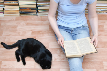 A girl sits on the floor and reads a book next to a black cat lying. Close-up