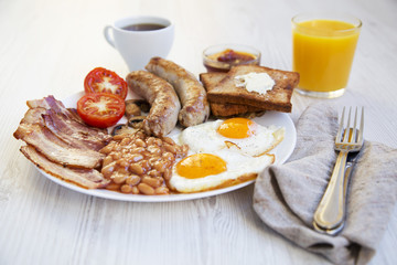 Full english breakfast with fried eggs, bacon, sausages, beans and toasts on white wooden background. Closeup. Side view.