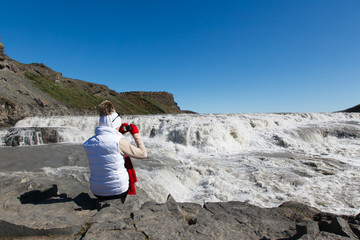 a unknown female tourist sits on a rock and takes pictures of a waterfall Dettifoss in Iceland