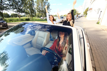 three girls driving in a convertible car and having fun.