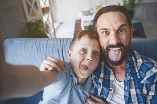 Portrait of happy boy and optimistic dad shoving tongues while taking selfie