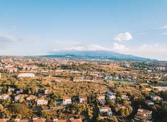 Beautiful aerial view on the Catania city with Etna volcano on the background by the sea. Small houses and beautiful narrow streets of Sicily.