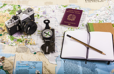 Compass, passport, photo camera and block notes on map