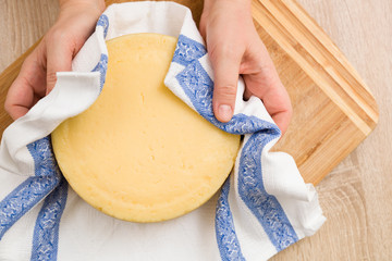 Top view on head of homemade cheese in man's hands.