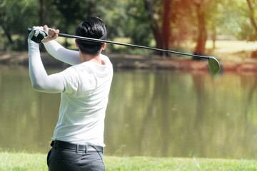 The back of golf Player in white shirt swinging glof. Young man practicing his swing on the golf course.