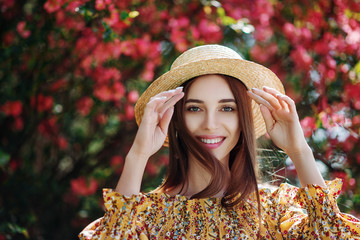 Outdoor close up portrait of young beautiful happy smiling girl with healthy white teeth, radiant clean skin, long natural hair. Model posing in flowering garden. Beauty, health concept. Copy space
