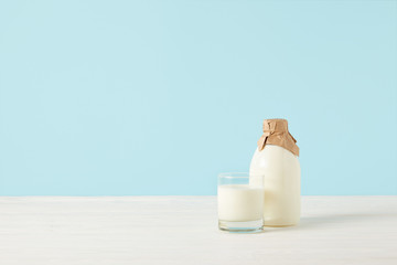 milk glass and milk in bottle wrapped by paper on blue background