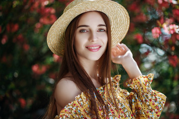 Outdoor close up portrait of young beautiful happy smiling girl with healthy white teeth, radiant clean skin, long natural hair. Model posing in flowering garden. Beauty, health care concept