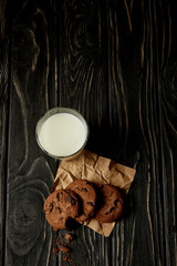 top view of chocolate cookies on crumpled paper and milk glass on black wooden surface