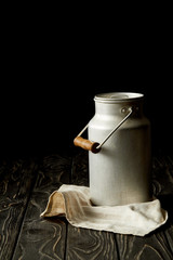closeup view of milk in aluminium can on sackcloth on black background