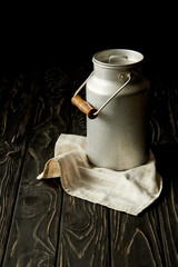 closeup image of milk in aluminium can on sackcloth on black background
