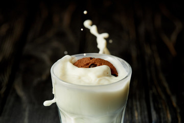 closeup view of chocolate cookie in milk glass with splashes on black wooden surface