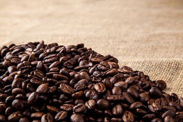 Pile of roasted coffee beans on a hessain cloth