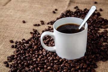 White coffee mug with coffee beans on hessian sack cloth