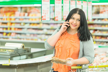 Closeup portrait of pretty young caucasian woman brunette talking on the phone and choosing goods in supermarket store