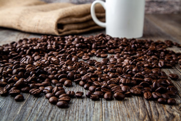 Pile of roasted coffee beans on a wooden table with hessain sack in background