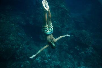 Wall Mural - partial view of man diving in ocean alone