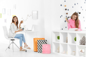 Young women with credit cards using laptop and tablet computer indoors. Internet shopping concept