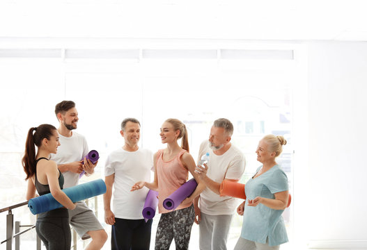 Group of people talking after yoga class indoors