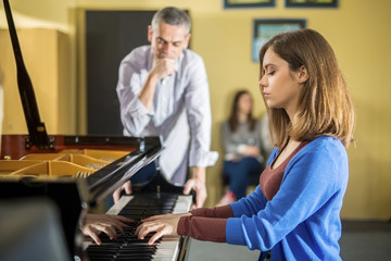 Young woman having piano class with her teacher.