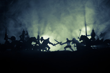 Medieval battle scene with cavalry and infantry. Silhouettes of figures as separate objects, fight between warriors on dark toned foggy background. Night scene. Wall mural