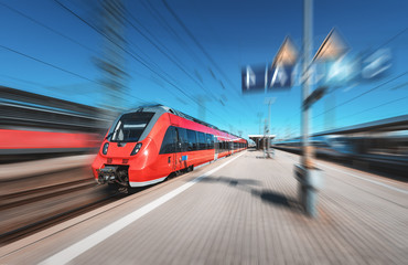 High speed red train in motion on the railway station at bright day. Modern intercity train with motion blur effect on the railway platform. Industrial. Passenger commuter train on railroad. Travel